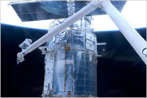 Grunsfeld y el Hubble con la Tierra al fondo - NASA