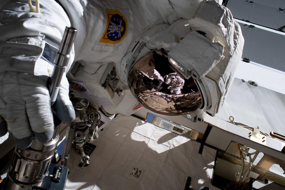 Christina Koch reflejada en el casco de Jessica Meir - NASA