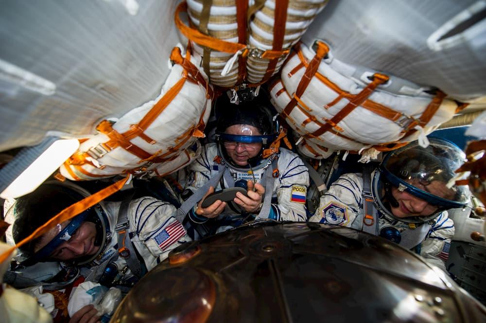 La tripulación de la Soyuz MS-15 esperando a que les ayuden a salir de la cápsula – NASA/GCTC/Andrey Shelepin