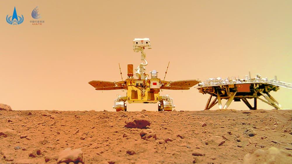 El rover Zhurong sobre la superficie de Marte en primer plano y más atrás y a la derecha su plataforma de aterrizaje – CNSA/PEC